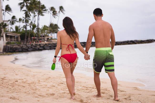 Vista posteriore di coppia che cammina mano nella mano sulla spiaggia — Foto stock