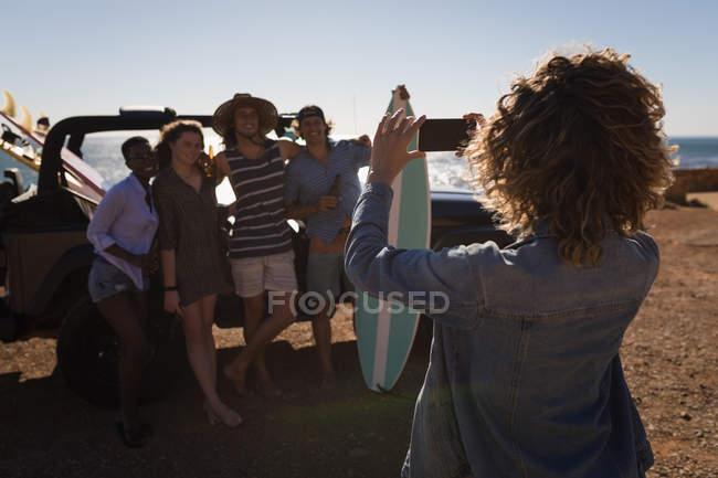 Femme ami en cliquant sur les photos d'amis avec téléphone portable dans la plage — Photo de stock