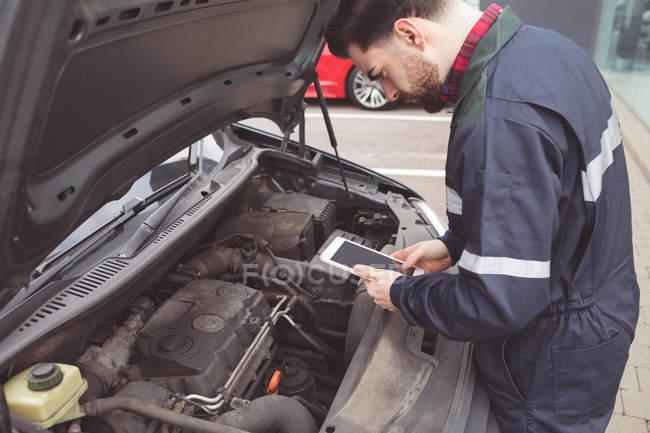 Male mechanic using digital tablet at repair garage — Stock Photo