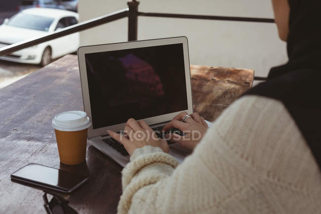 Mid section of urban hijab woman using laptop in pavement cafe — Stock Photo