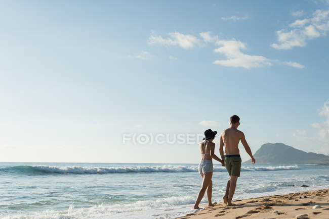 Couple walking together hand in hand at beach — Stock Photo
