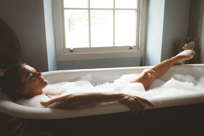 Woman taking a bubble bath in bathroom at home — Stock Photo