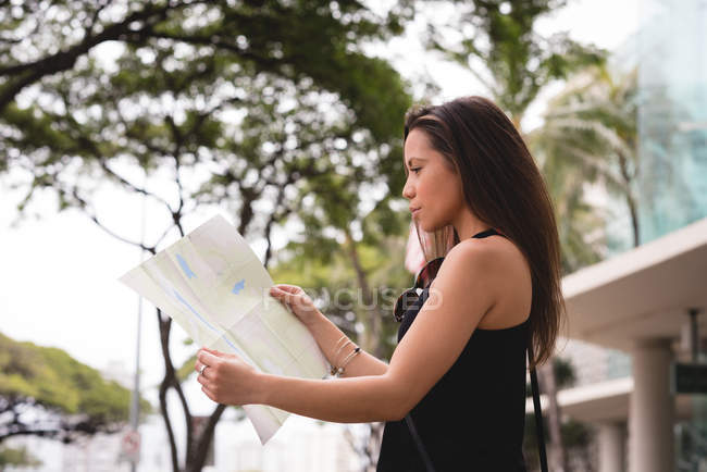 Beautiful woman looking at map in city street — Stock Photo