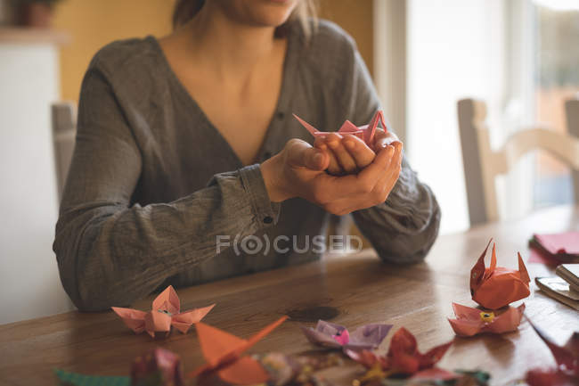 Mid section of woman showing origami at home — Stock Photo