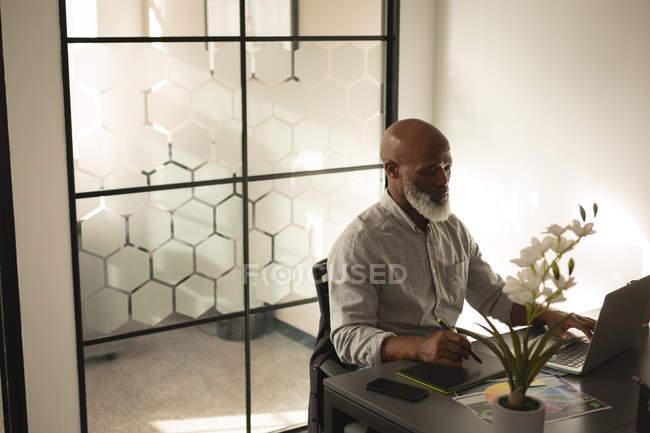 Senior designer grafico utilizzando la tavoletta grafica e computer portatile allo scrittorio in ufficio — Foto stock
