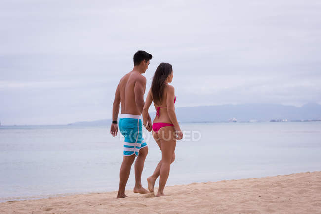Romantic couple walking hand in hand at beach — Stock Photo