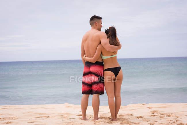Вид сзади пара, обнимая друг друга на пляже — стоковое фото