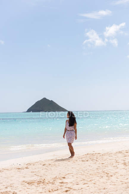 Woman walking alone in the beach on a sunny day — Stock Photo