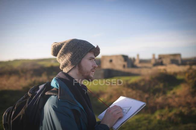 Junge männliche Wanderer stehen mit Notizblock auf dem Land — Stockfoto