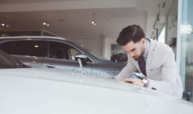 Bello venditore esaminando auto presso showroom — Foto stock