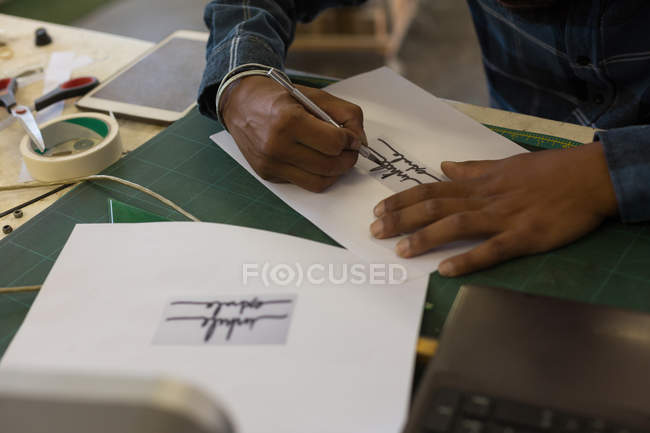 Man making design on paper in workshop — Stock Photo