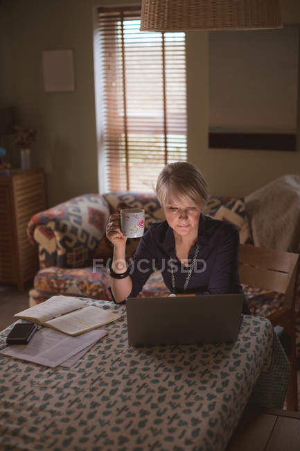Mature woman using laptop while having coffee in living room at home — Stock Photo