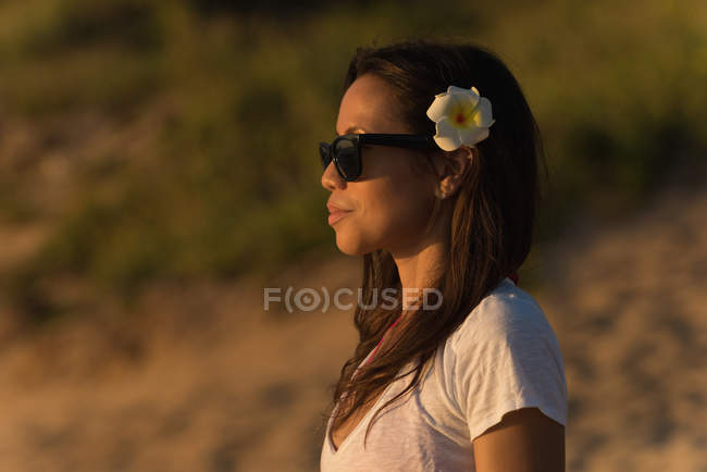 Thoughtful woman standing in the beach at dusk — Stock Photo