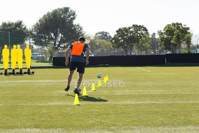 Jugador de fútbol dribbling a través de conos en el campo de los deportes - foto de stock