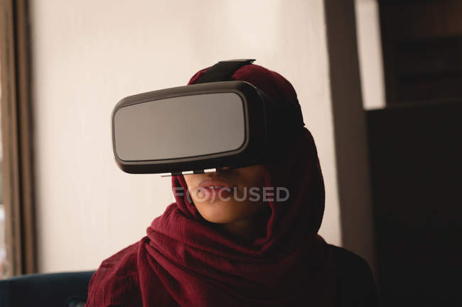 Businesswoman in hijab using virtual reality headset at office cafeteria — Stock Photo