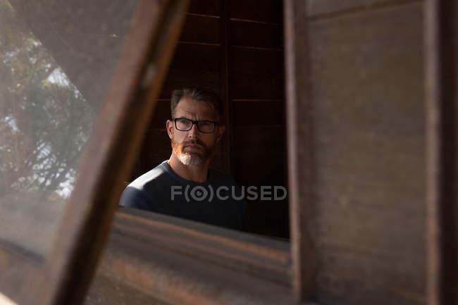 Uomo che guarda attraverso la finestra in capanna di legno — Foto stock