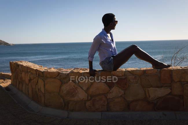 Задумчивая женщина отдыхает на пляже в солнечный день — стоковое фото
