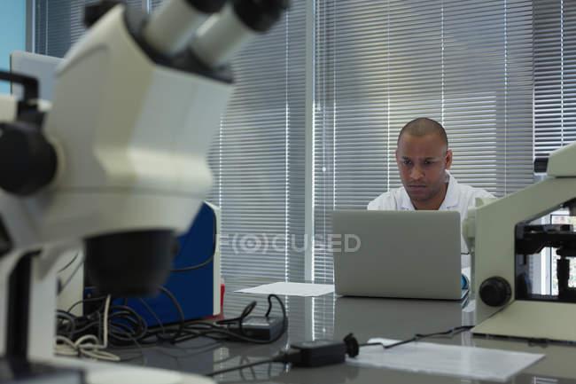Wissenschaftler mit Laptop am Schreibtisch im Wissenschaftslabor — Stockfoto