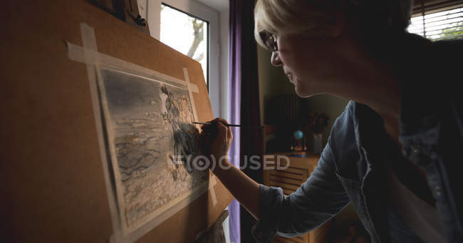 Beautiful mature woman artist painting picture at home — Stock Photo