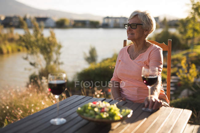 Thoughtful senior woman relaxing in the backyard — Stock Photo