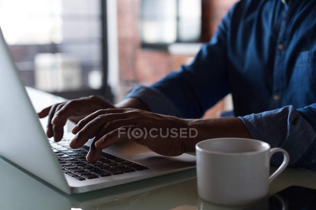 Mid section of senior man using laptop at home — Stock Photo