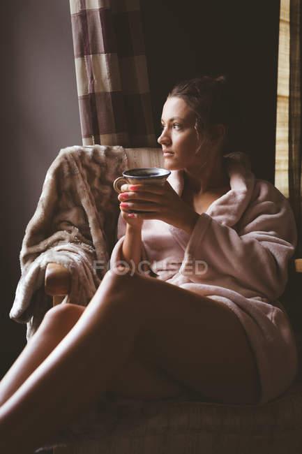 Продуманий одна жінка кави у вітальні на дому — стокове фото