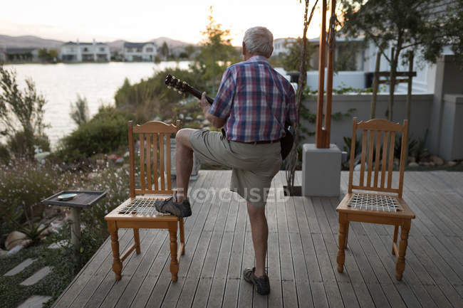 Senor man playing guitar in the porch at home — Stock Photo