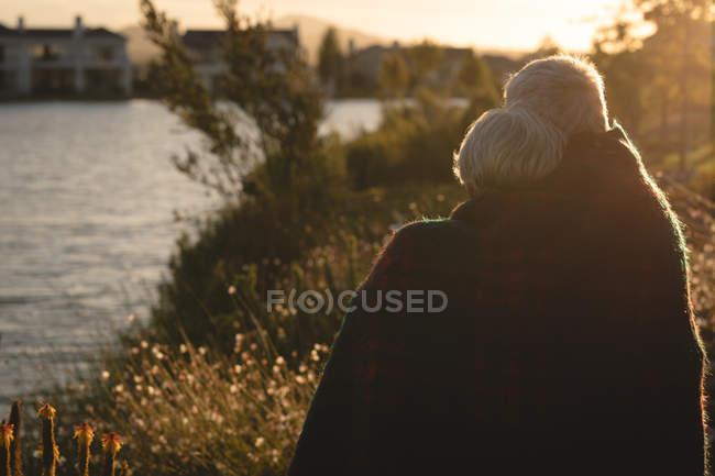 Rückansicht des Älteres Paar in Decke entspannend im Hinterhof — Stockfoto