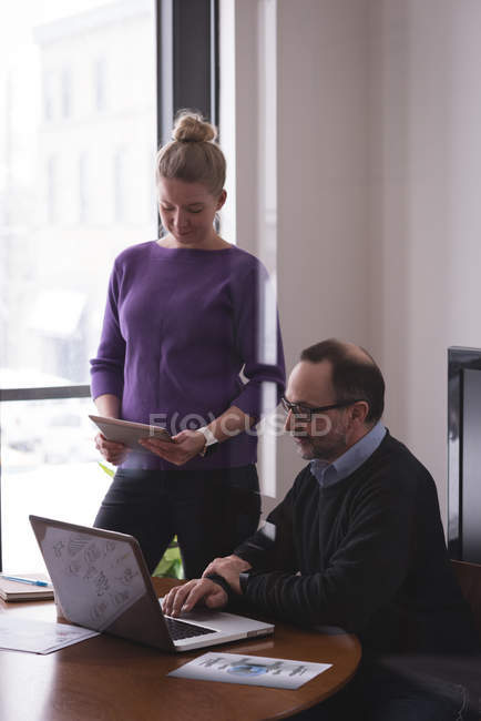Business colleagues working on laptop and digital tablet in office — Stock Photo