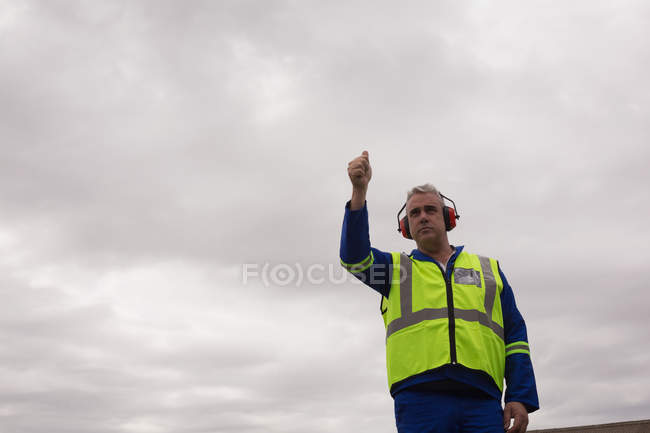 Crew member showing thumbs up in airport — Stock Photo