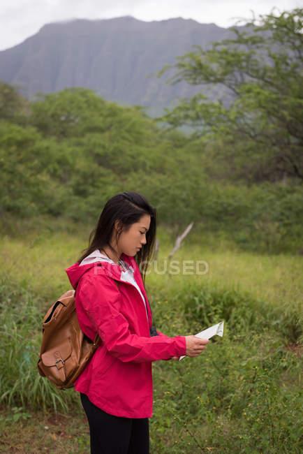 Bella donna guardando la mappa in campagna — Foto stock