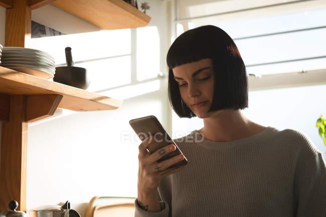 Femme utilisant un téléphone portable dans la cuisine à la maison — Photo de stock