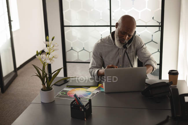 Senior graphic designer talking on mobile phone at desk in office — Stock Photo