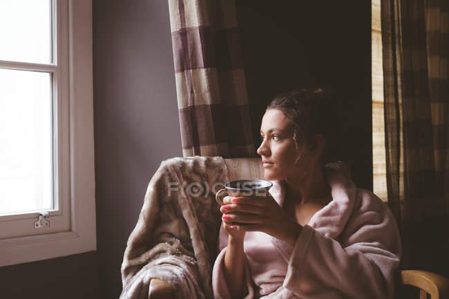Femme réfléchie prenant un café dans le salon à la maison — Photo de stock