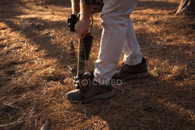 Hunter regolazione arco e freccia nella foresta in una giornata di sole — Foto stock