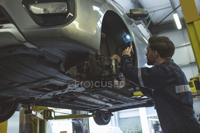 Чоловічий механік вивчення автомобіль з факелом у ремонт гаража — стокове фото