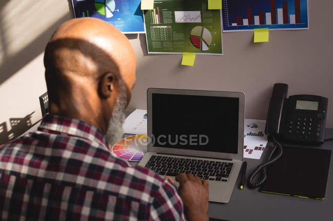 Senior graphic designer using laptop at desk in office — Stock Photo