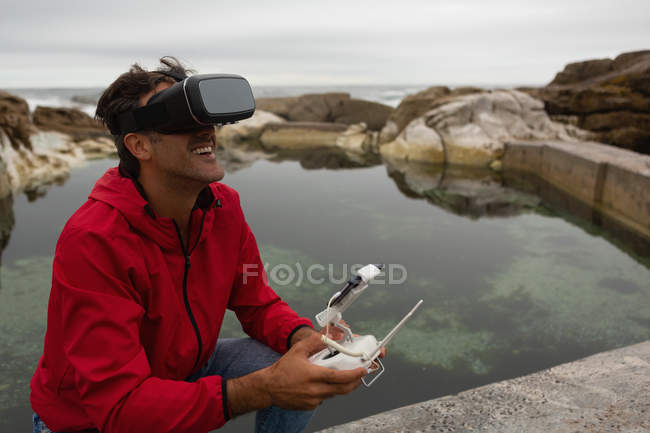 Man operating a flying drone while using virtual reality headset in countryside — Stock Photo