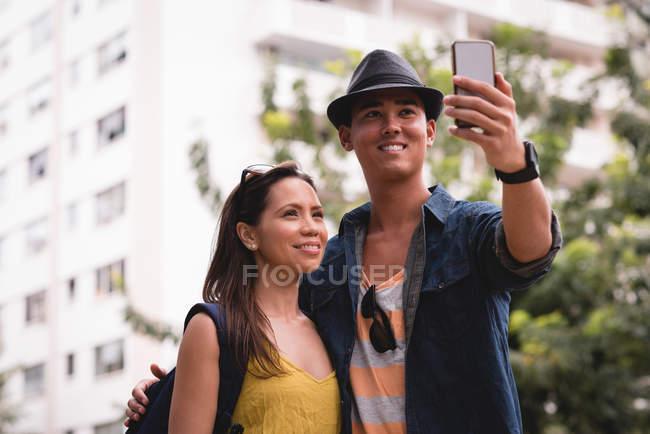 Couple prenant selfie avec téléphone mobile dans la ville — Photo de stock