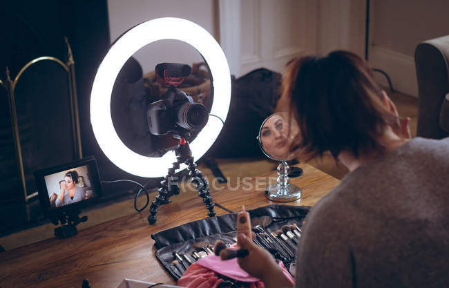 Female video blogger applying make up on face at home — Stock Photo