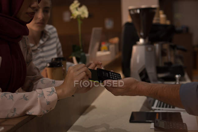 Hijab woman making payment through NFC in cafeteria at office — Stock Photo