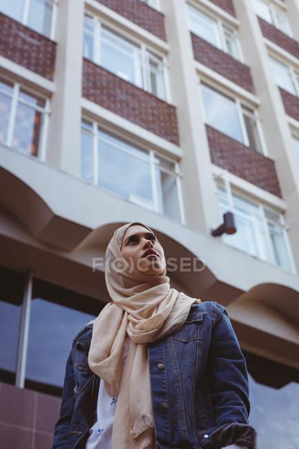Vista basso angolo di hijab donna in piedi contro edificio — Foto stock