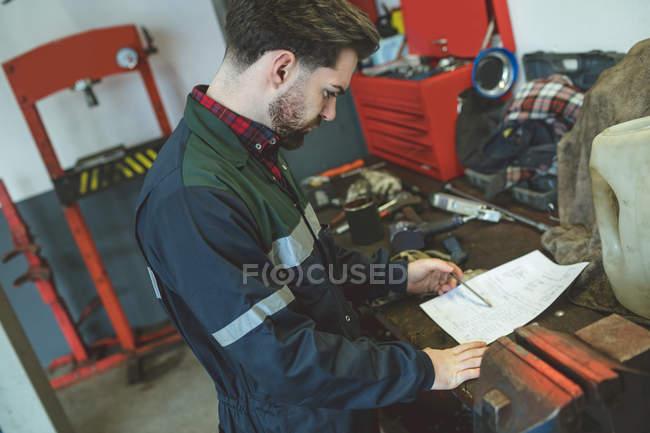 Attentive mechanic reading instruction manual in repair garage — Stock Photo