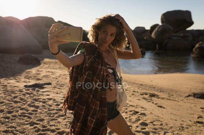 Femme prenant selfie avec téléphone mobile à la plage par une journée ensoleillée — Photo de stock