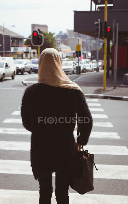 Vista posteriore della donna di hijab che camminano sulle strisce pedonali — Foto stock