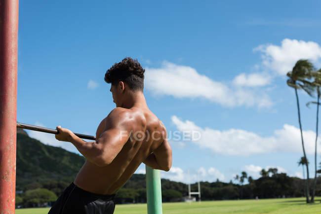 Молодой человек, тренирующийся на горизонтальной полосе в парке — стоковое фото