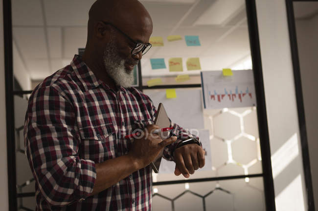 Senior graphic designer using smartwatch in office — Stock Photo