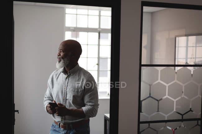 Старший дизайнер, с помощью мобильного телефона в офисе — стоковое фото
