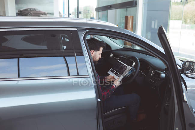 Salesman reading brochure inside the car at showroom — Stock Photo