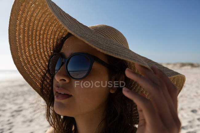 Thoughtful woman in hat standing at beach — Stock Photo